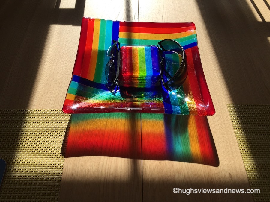 Photo of a colourful dish on a table reflecting a colourful shadow.