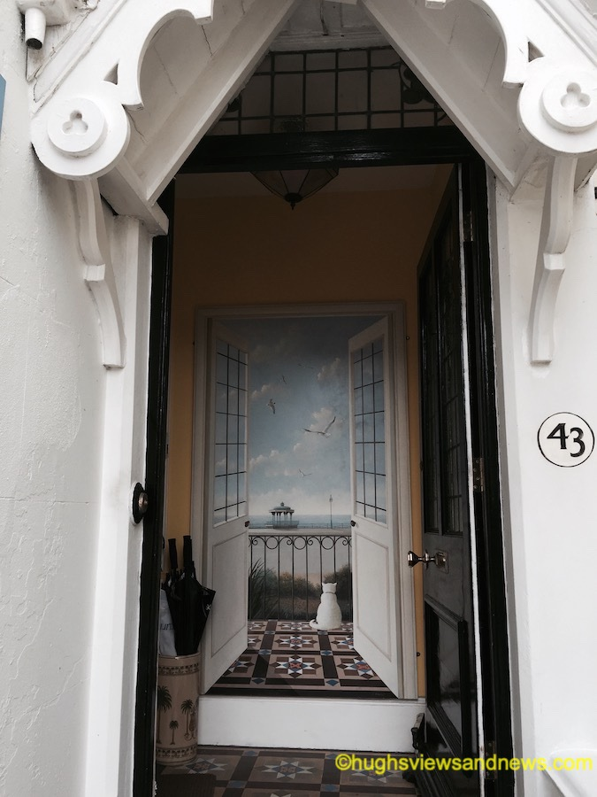 Photo of a black opened door that shows a painting of two slightly jarred opened glass-panelled, white doors that look out on a white cat sat on a balcony that looks towards the sea